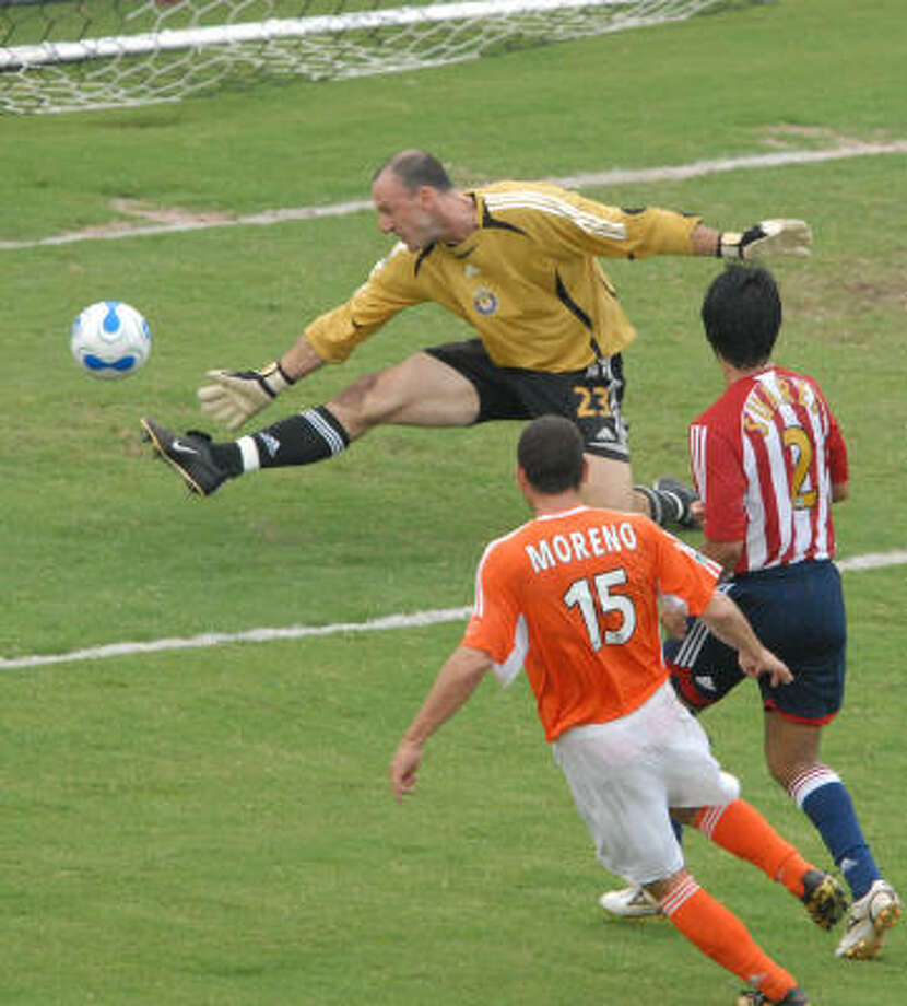 Dynamo's Alejandro Moreno scores against Chivas USA's  goalkeeper Presto Burpo during the second half. Photo: CARLOS JAVIER SANCHEZ, FOR THE CHRONICLE