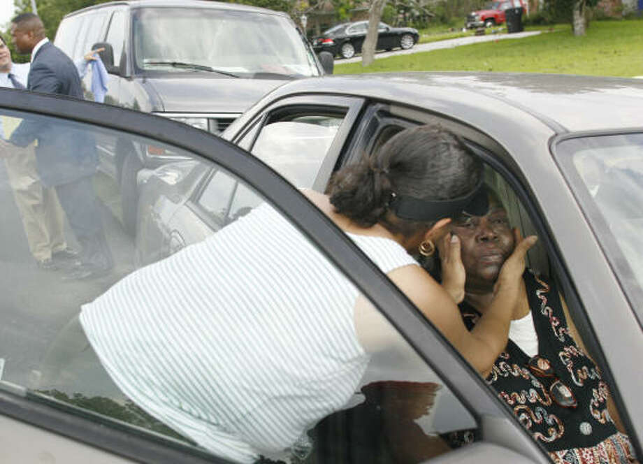 The mother of Bilford Dwight Junious, rape and serial killing suspect, is comforted by a family member after a press conference at Bilford's home. Photo: Mayra Beltran, Chronicle