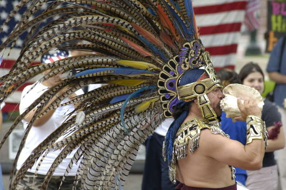 Manuel Sanchez was among the Aztec-style dancers marching downtown for immigration reform Monday. Photo: Carlos Javier Sanchez, FOR THE CHRONICLE