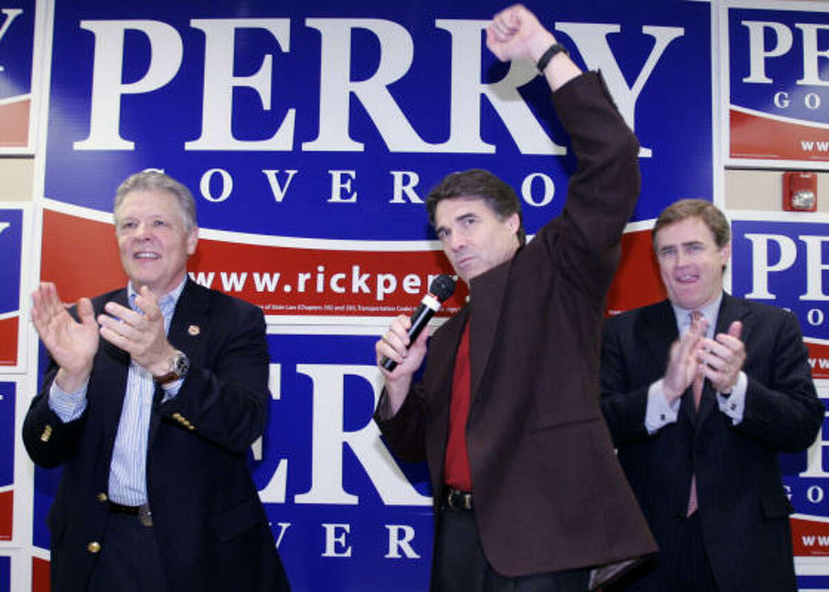 Dallas County Republican Party official Kenn George, left, and Rep. Dan Branch, R-Dallas, right, clap as Texas Gov. Rick Perry, center, gestures while addressing attendees during one of his