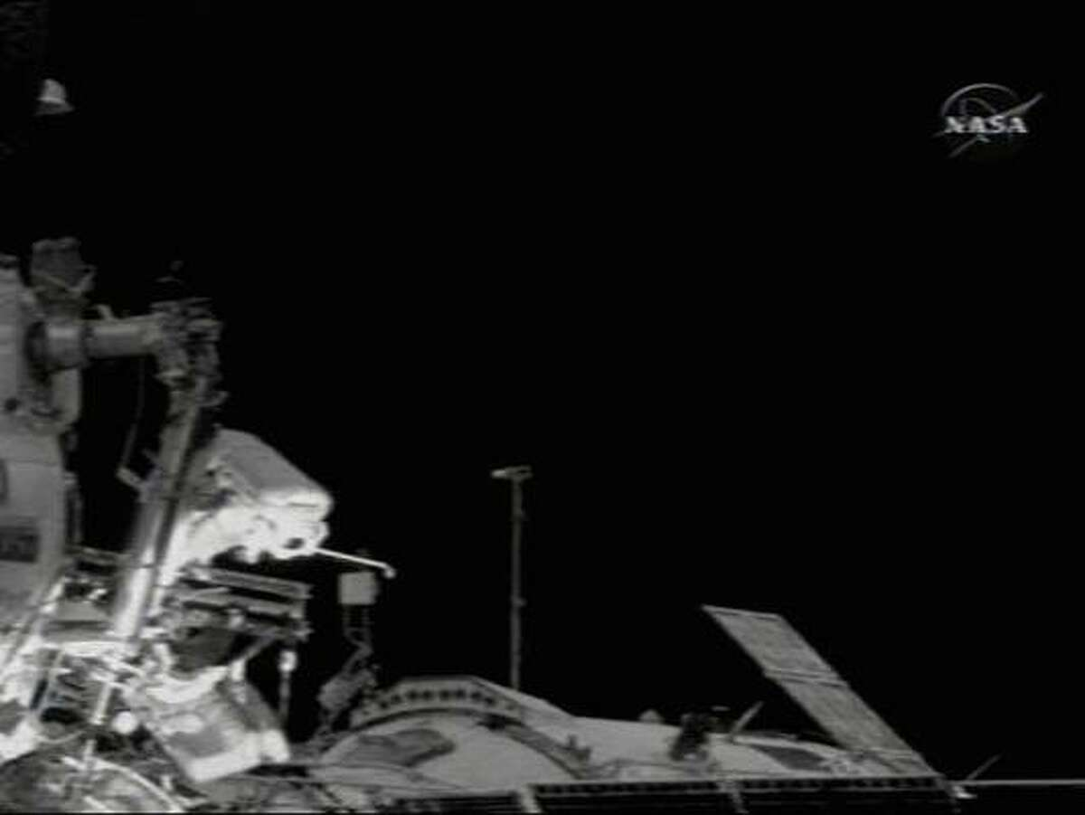 In a frame capture from NASA TV, spacewalker Mikhail Tyurin holds a gold six iron as he stands on the PIRS docking compartment's
