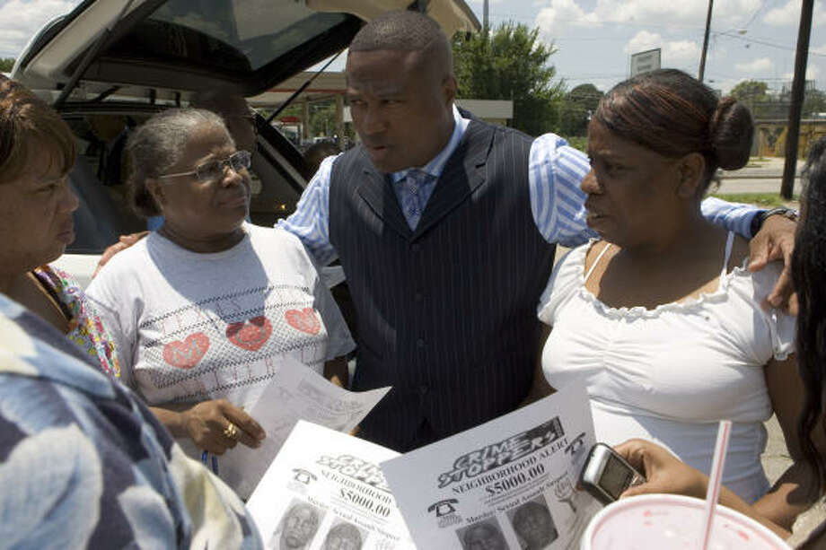 Community activist Quanell X, center, speaks with Chrys Hudson, left, Ruth Burns and Renay Norris as he hands out fliers seeking an alleged serial killer in the Acres Home neighborhood on Friday. Photo: BRETT COOMER, CHRONICLE