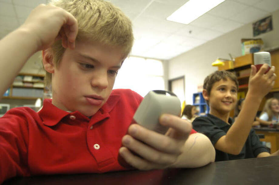 Sixth-graders Adam Carlin, left, and Sean Ulmer use the Qwizdom system in their science class at Brookside Intermediate School in Friendswood. The system lets students take tests and answer questions using a handheld remote. Sean likens it to playing a video game. Photo: Johnny Hanson, For The Chronicle