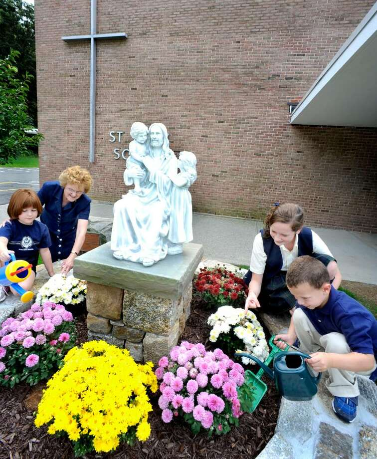 Saint Mary School principal Sister Anne McCarthy, center left, supervises students: Judy Apotheker, first grade, left, Molly Gallagher, eighth grade, center right, and Anthony Manca, jr., kindergarten, right, caring for plants on Wenesday, Sept. 9, 2009, around a statue built in front of the Bethel school in honor of being named by the U.S. Dept. of Education as a Blue Ribbon School. Photo: Michael Duffy / The News-Times