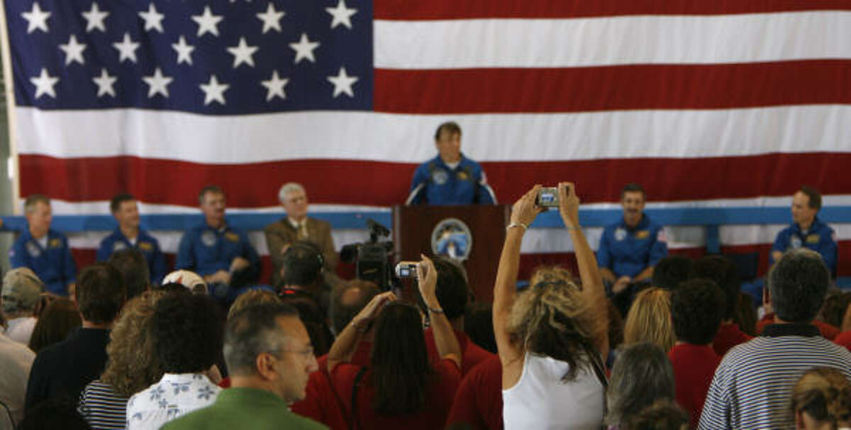 A woman takes a photo of Heide Stefanyshyn-Piper (at the podium) moments before she fainted for the first time at Ellington Field today.