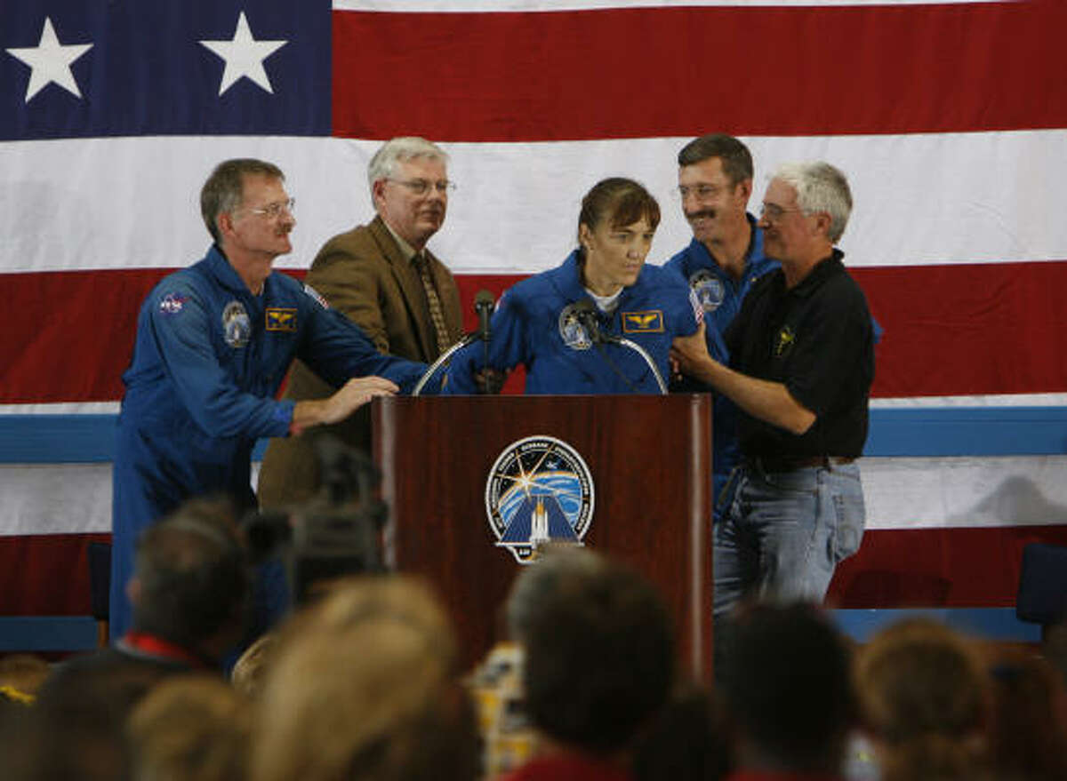 Astronaut Joe Tanner, far left, and Dan Burbank, right, and two other unidentified men help Heide Stefanyshyn-Piper as she faints at a shuttle ceremony in Houston today.