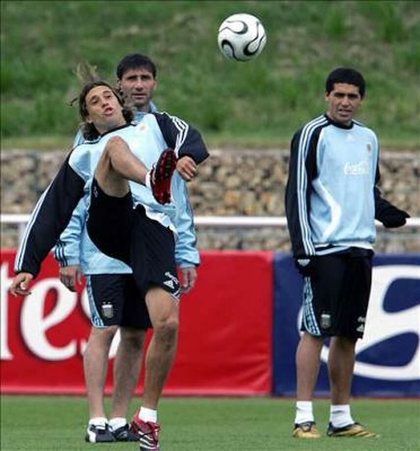 Argentinean player Hernan Crespo kicks the ball as goalkeeper Roberto Abbondanzieri and Juan Roman Riquelme looks on during a training session at HerzogsPark trining camp in Herzogenaurach 06 June 2006. Argentina will face Ivory Cost on June 10 in their fisrt match for the group C of the World Cup Germany 2006.  AFP PHOTO  / DANIEL GARCIA Photo: DANIEL GARCIA, AFP
