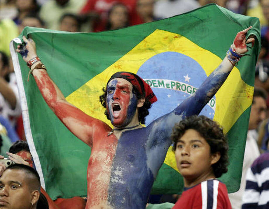 An FC Barcelona fan cheers as his team takes the pitch for an international friendly football match against Club America in Houston. Photo: Dave Einsel, AFP/Getty Images