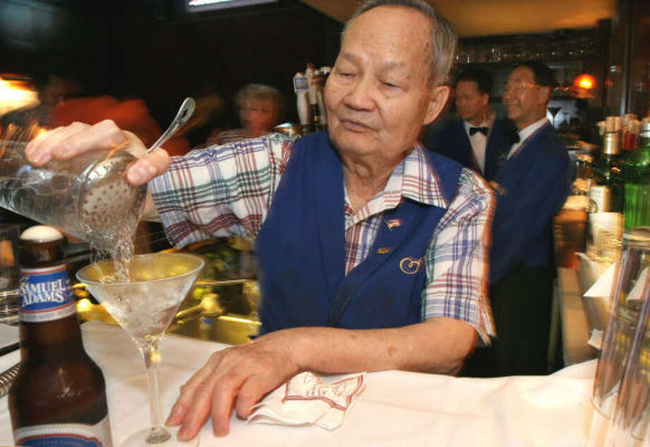 Hoy Wong, who has been working as a bartender for 58 years, makes a martini at the Algonquin Hotel's Blue Bar in New York. ''He never misses a day,'' said the hotel's general manager. Photo: TINA FINEBERG, AP