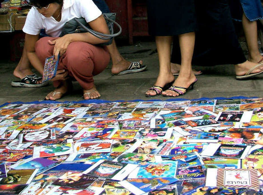 Customers browse for a pirated CDs on sale in July at a busy sidewalk in downtown Yangon, Myanmar. Photo: AP