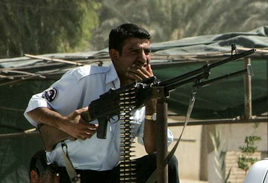 An Iraqi police officer holds a weapon aboard a police car while securing a road as U.S. troops from the 1st Brigade Combat Team, 4th Infantry Division, turned over the security of Tarmiya district to the Iraqi police in Baghdad. Photo: THAIER AL-SUDANI, REUTERS