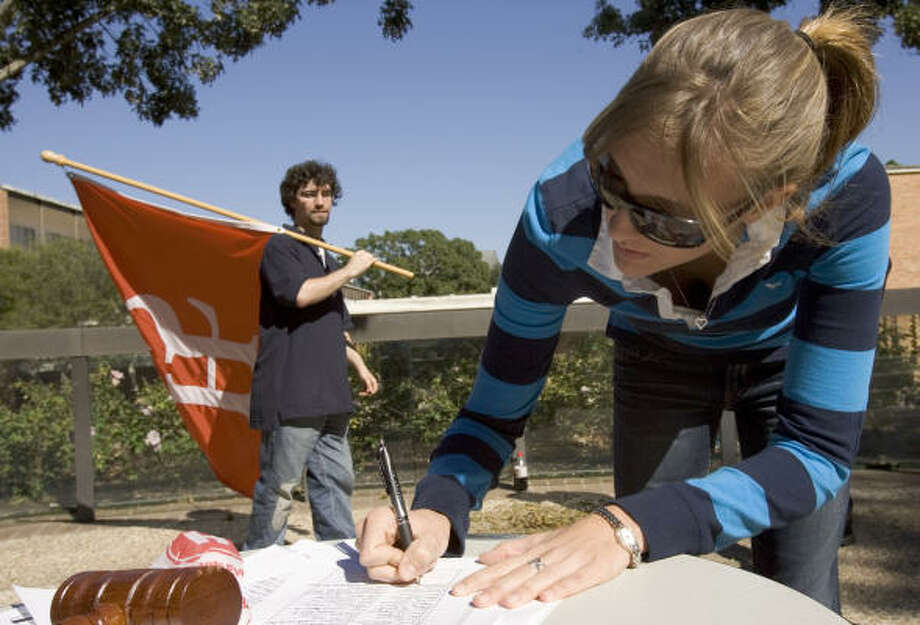 Lauren Edwards, a junior at Sam Houston State University, signs a petition on the Huntsville campus recently urging the Legislature to preserve the school's name. Behind her, Ryan Hess, a sophomore from Magnolia, carries a school flag. Photo: BRETT COOMER, CHRONICLE