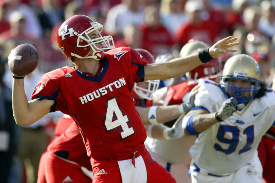 University of Houston quarterback Kevin Kolb (4) throws for a first down as Tulsa defender Robert Lau (91) closes in. Photo: Jessica Kourkounis, For The Chronicle