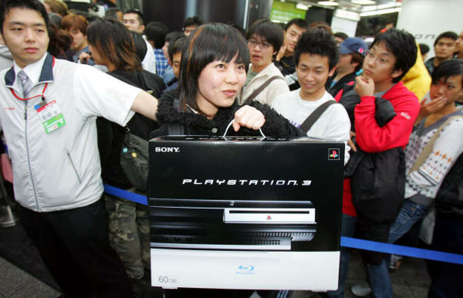 Cheng Cheng, a Chinese customer, is surrounded by envious buyers as she carries her PlayStation 3 video game console at a Tokyo electronics store at the Sony device's debut on Saturday. The company admitted on Tuesday that the new console can't run some of the titles designed for previous versions of PlayStation, even though the new machine was marketed as being fully compatible. Photo: KOJI SASAHARA, AP