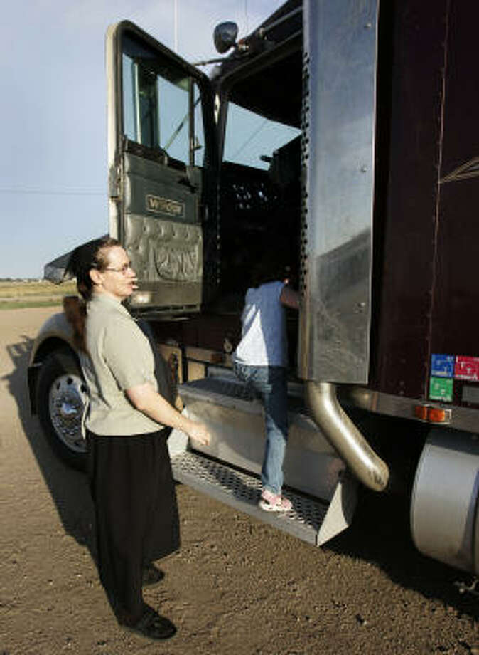 Justina Giesbrecht and her daughter, Christyna, climb into a truck at their home near Sublette, Kan. Giesbrecht said growing up in the colony in Mexico did little to prepare her for life outside. Though she wore only dresses in Mexico, she now sometimes wears pants and drives a semi for her husband's trucking business. Photo: ORLIN WAGNER, AP