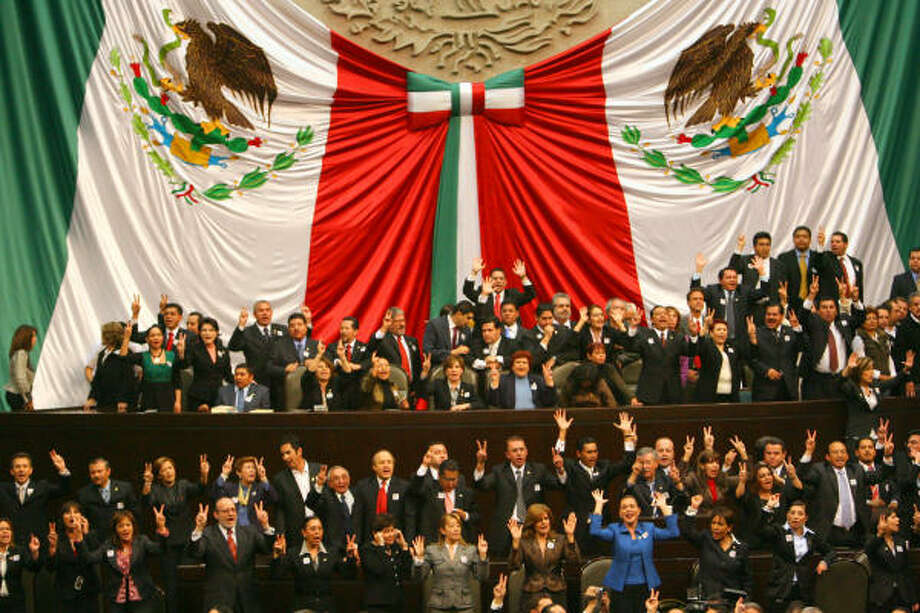 Mexican lawmakers who support new President Felipe Calderon raise their hands calling for peace during Calderon's swearing-in ceremony today. Photo: EDWARD A. ORNELAS, SAN ANTONIO EXPRESS-NEWS