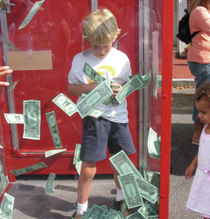 A boy tries to grab all the money he can at last year's sidewalk sale. The money machine is an annual tradition by the Bank of New Canaan. Photo: Contributed Photo