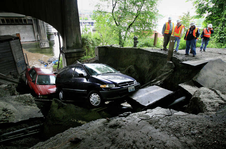 Under the University Bridge, city utility employees look over the scene 