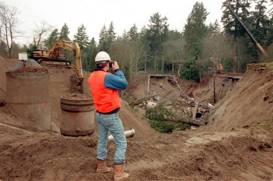 Ed Heavey, project geotechnical engineer for reconstruction, takes a   photo of the sinkhole in Shoreline, north of Seattle, that opened on  Dec. 31, 1996. Water released from a broken sewer pipe washed away the  glacial sand under the road. Photo: Grant M. Haller / Seattle Post-Intelligencer