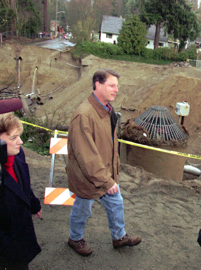 Vice President Al Gore walks past a giant sinkhole in Shoreline on Jan.  10,  1997, during his inspection of damage from recent  storms in the  West. At Gore's side is Sen. Patty Murray,  D-Wash. (AP Photo/Elaine  Thompson)
