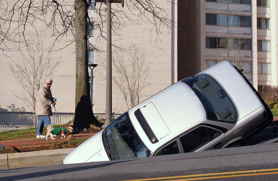 A woman walks her dog past a car caught in a sinkhole caused by a broken