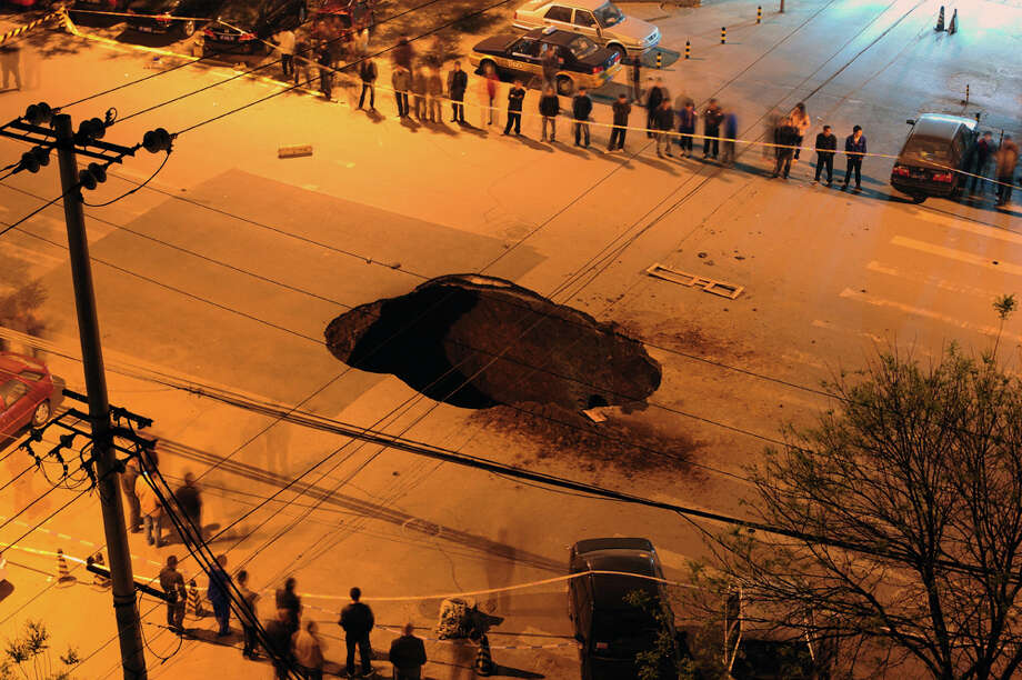 Workers block off the site of a sinkhole which occurred overnight on  Shiliuzhuang road, in Beijing on April 26, 2011. A section of the road  collapsed beneath a truck, slightly injuring the driver and a passenger,  who both jumped out the vehicle before it sank into the hole, as an  authority suspects the hole was caused by the construction of a subway  line.