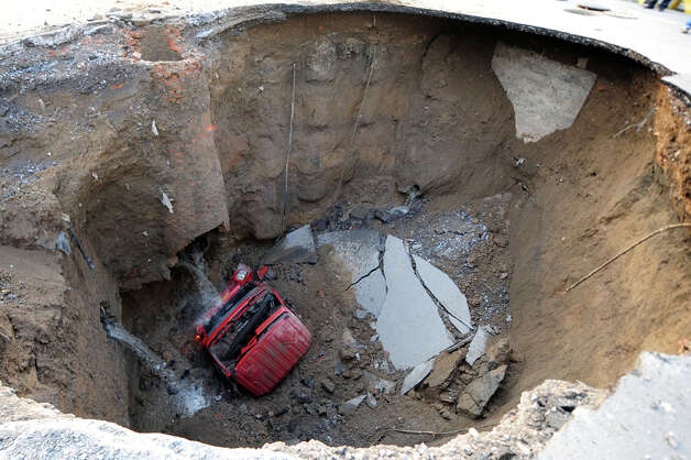 A truck lies in a sinkhole which occurred overnight on Shiliuzhuang  road, in Beijing on April 26, 2011. A section of the road collapsed  beneath a truck, slightly injuring the driver and a passenger, who both  jumped out the vehicle before it sank into the hole, as an authority  suspects the hole was caused by the construction of a subway line. / 2011 AFP
