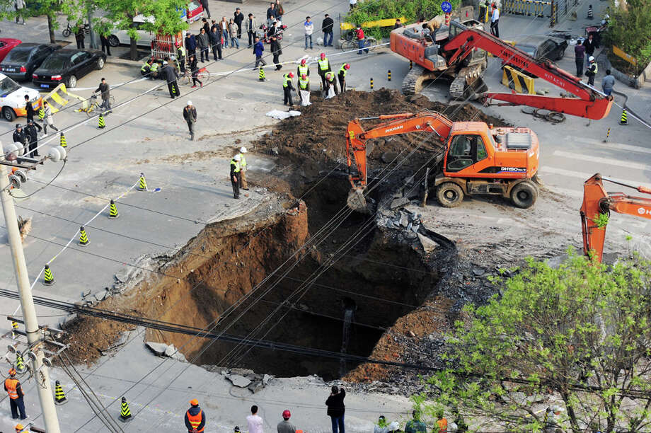 Workers use excavators to fill in a sinkhole which occurred overnight on  Shiliuzhuang road, in Beijing on April 26, 2011. A section of the road  collapsed beneath a truck, slightly injuring the driver and a passenger,  who both jumped out the vehicle before it sank into the hole, as an  authority suspects the hole was caused by the construction of a subway  line. / 2011 AFP