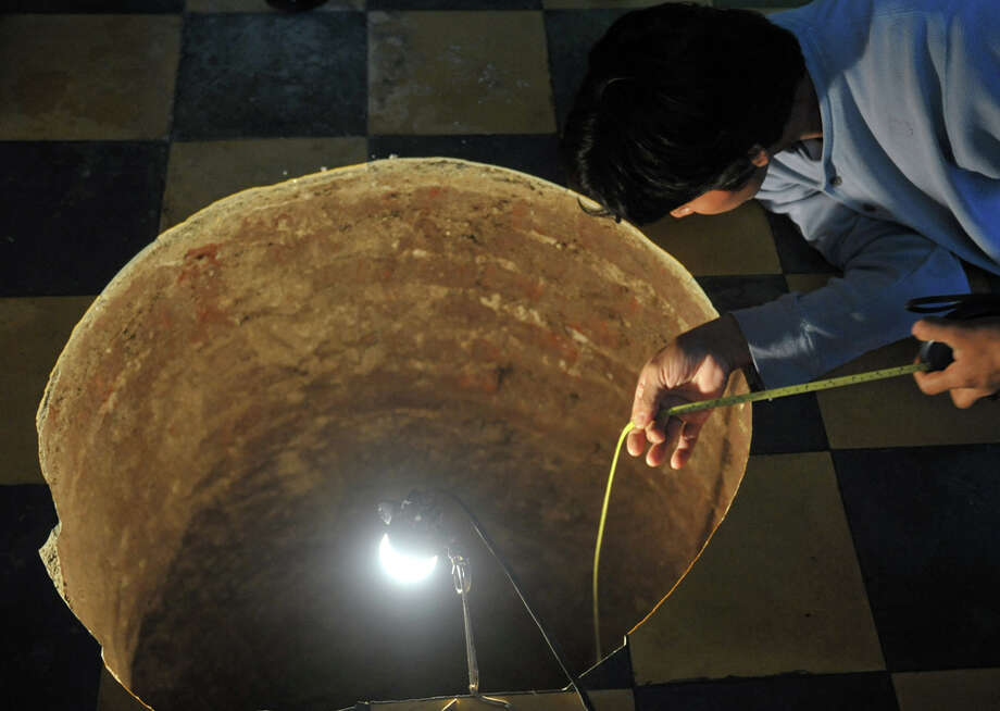 A man inspects a sinkhole inside a house on July 19, 2011, north of 