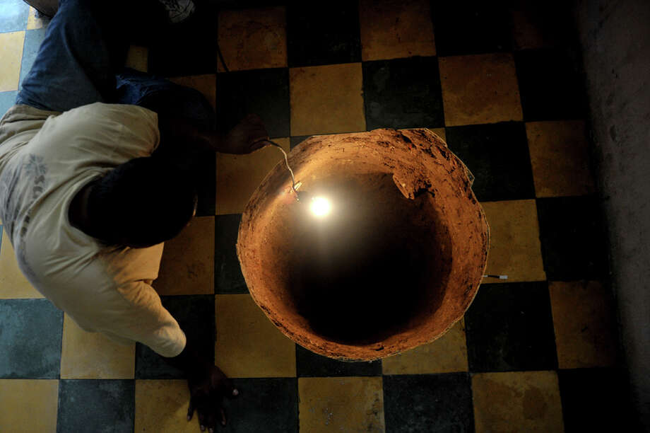 A man inspects a sinkhole formed in a house on July 19, 2011, north of 
