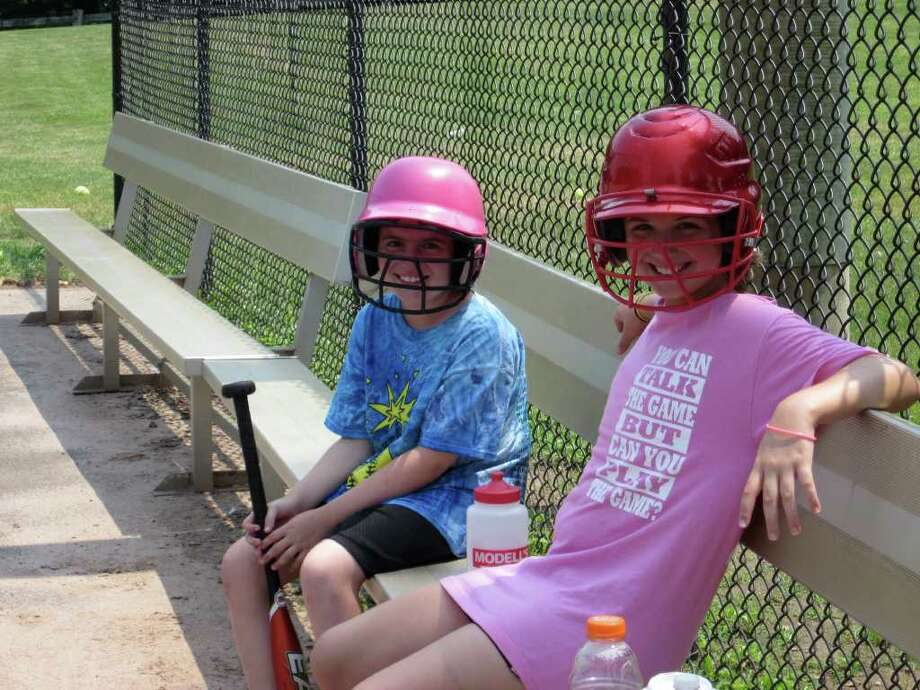 Molly Murray and Rebecca Schwartz of New Canaan take a break during batting practice. The two girls were taking part in the Bobby Valentine sports camp at Waveny Park. - Photo by John H. Palmer Photo: File Photo