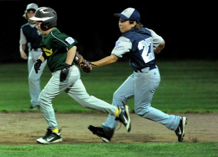 Highlights from Little League All-star baseball action between Westport and Edgefield in Shelton, Conn. on Thursday July 14, 2011. Westport's #27 Chad Knight tags out Edgefield's #16 Josh Nichilly in a run down play between first and second. Photo: Christian Abraham / Connecticut Post