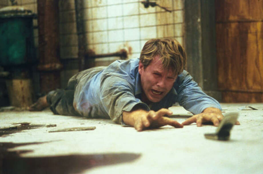 Lawrence (Cary Elwes) is dying to make a phone call in Saw. Photo: Greg Gayne, Lions Gate