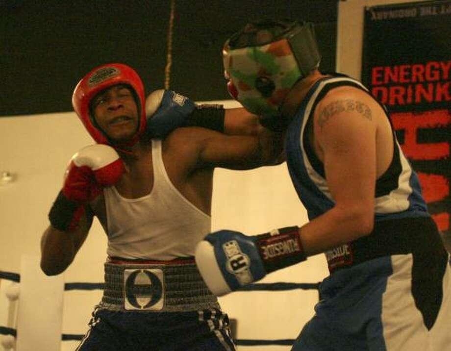Lanard Lane, left, absorbs this blow from Jose Vizueth before winning the Golden Gloves bout Saturday. Photo: KAREN WARREN, CHRONICLE