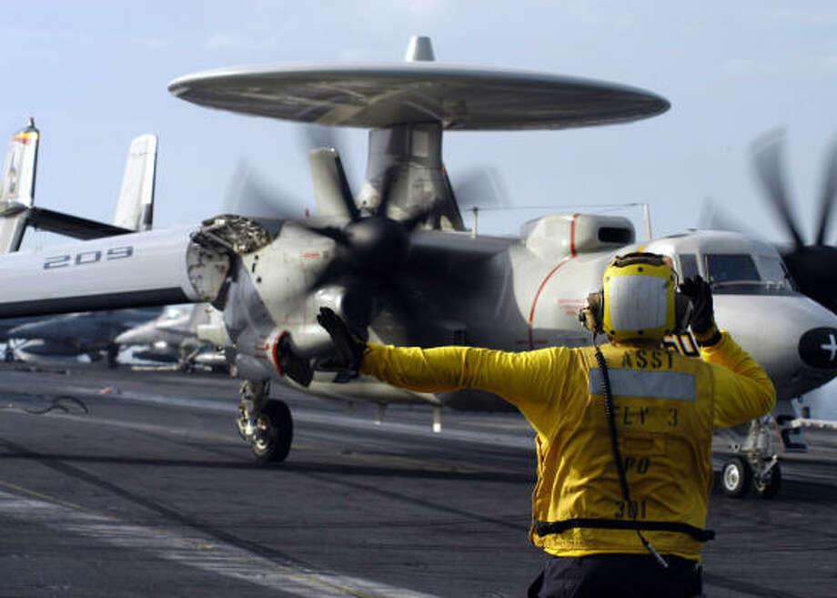 A crew member directs an E-2C Hawkeye on the flight deck of Nimitz-class aircraft carrier USS Dwight D. Eisenhower in the Persian Gulf. Photo: U.S. Navy