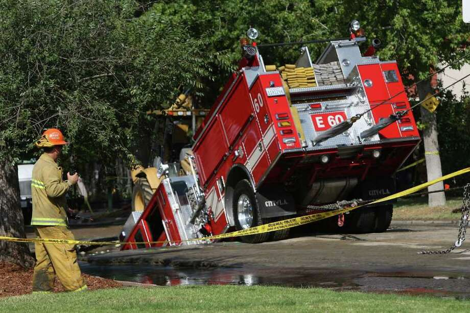 A 22-ton Los Angeles Fire Department fire truck protrudes from a sinkhole on September 8, 2009 in the Valley Village neighborhood of Los Angeles, California.  Photo: David McNew, Getty Images / 2009 Getty Images
