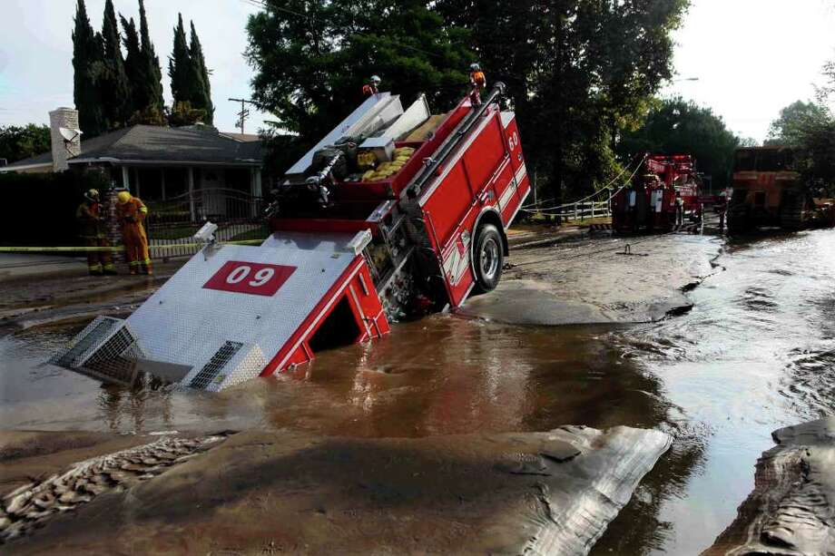 A Los Angeles fire truck is pulled from a sinkhole in the Valley Village neighborhood of Los Angeles Tuesday, Sept. 8, 2009. Four firefighters escaped injury early Tuesday after their fire engine sunk into a large hole caused by a broken water main in the San Fernando Valley, authorities said. Photo: Nick Ut, AP / AP