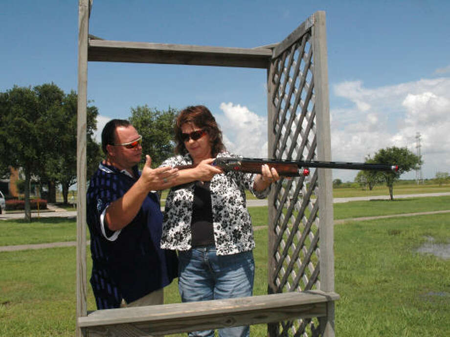 American Shooting Centers president and chief operating officer John ``Mo'' Parsons, left, instructs client Lynn Farrell on how to shoot skeet, where targets are projected into the air from the left and right sides at an angle of 45 degrees. Photo: George Wong, For The Chronicle