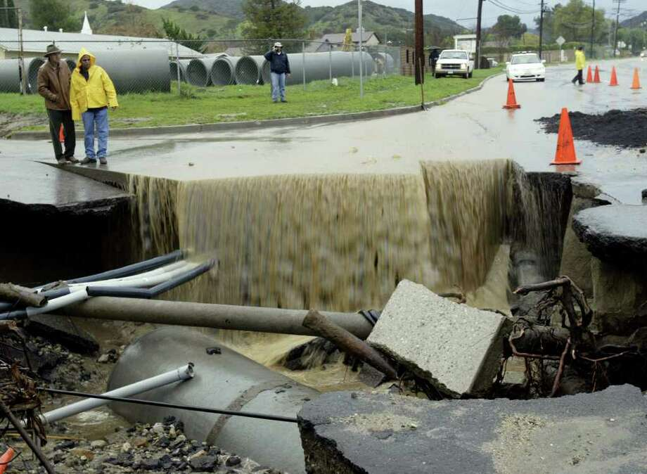 Workers watch flood waters pour into a construction site that turned into a sinkhole Wednesday, Dec. 29, 2004, in the Sun Valley section of Los Angeles. A powerful Pacific storm that bore floods, mudslides and record-breaking rainfall sent another pulse across Southern California early Wednesday, as Northern California prepared for another front expected to bring heavy snow and high winds to the Sierra Nevada and much of Eastern California. Photo: NICK UT, AP / AP