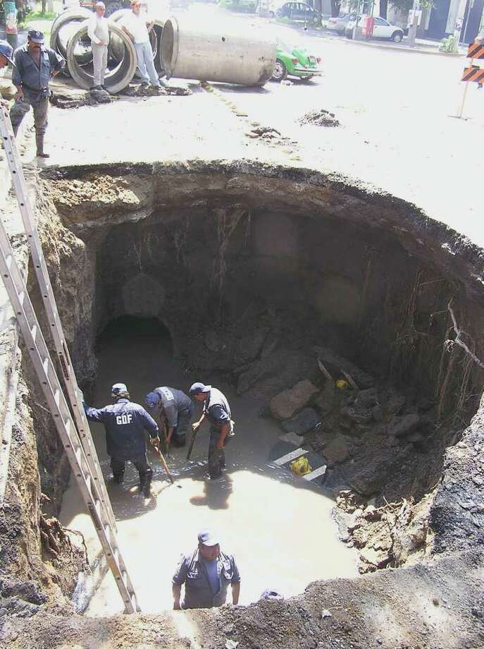Workers and onlookers Wednesday at a sinkhole that opened up on a four-lane Mexico City street. The sink hole, said to be caused by rain waters and a broken underground drainage pipe, opened up late Tuesday Sept. 14 , 2004, on Benjamin Franklin Street.    Dane Schiller/Staff Photo: DANE SCHILLER, SAN ANTONIO EXPRESS-NEWS / SAN ANTONIO EXPRESS-NEWS