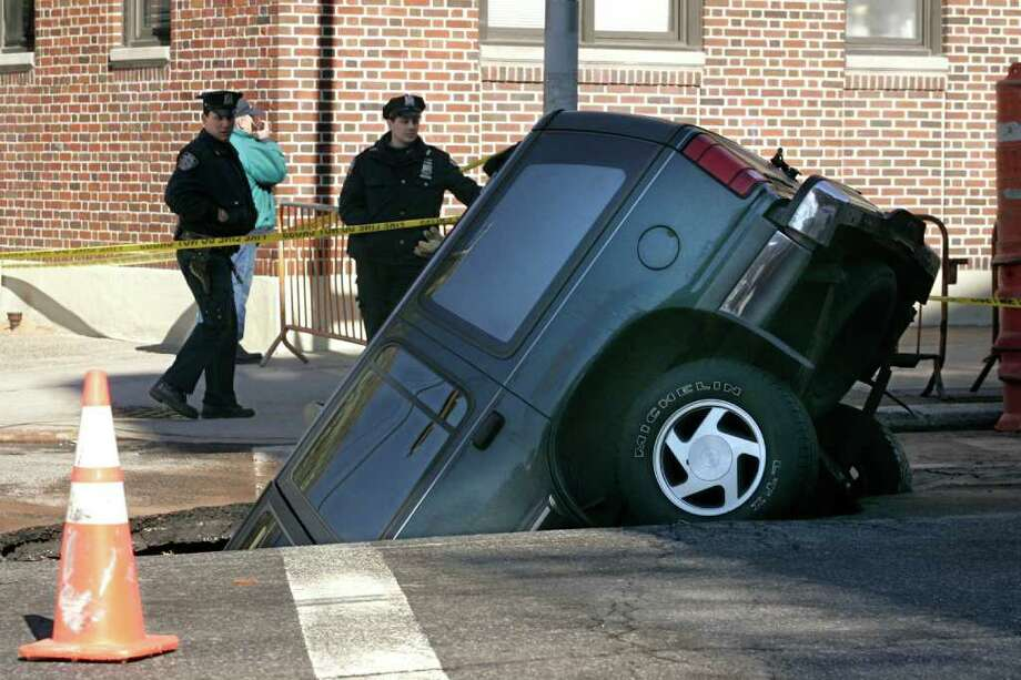 A sports utility vehicle is stuck in a sinkhole in the Brooklyn section of New York after a water main break caused the street to give way Monday, March 27, 2006. The driver of the vehicle was not seriously injured, according to the fire department. Photo: SHIHO FUKADA, AP / AP