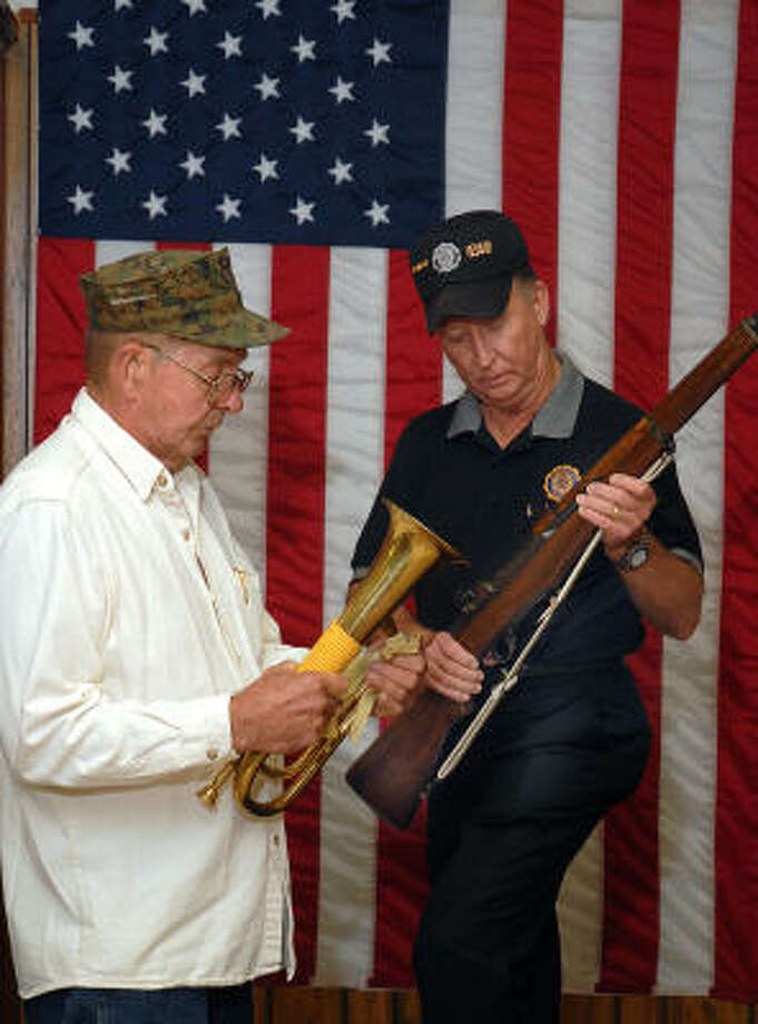 Veteran Bob Baker cleans his horn as fellow veteran Larry Eary examines his rifle. Baker performs taps on his horn during ceremonies. They are members of the American Legion Post 618, Willis, Honor Guard and participate in veterans' funerals and other community events. Photo: David Hopper, For The Chronicle