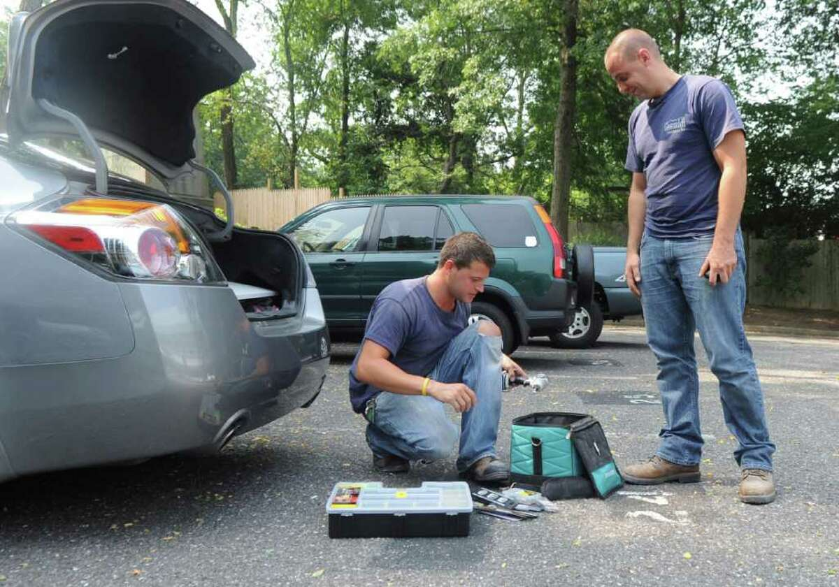 Bruno Demasi III, left, and Mike Daniele work in the heat for Gesualdi Construction Inc., of Stamford, in a parking lot off East Putman Avenue on Thursday, July 21, 2011.