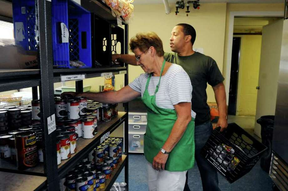 Volunteer Lisa Kralik, of Byram, and staff member Guy Pettiford stock cans at Neighbor to Neighbor on Thursday, July 21, 2011. Neighbor to Neighbor is one of the United Way of Greenwich's newest partners, recently receiving its first grant of $5,000. Photo: Helen Neafsey / Greenwich Time