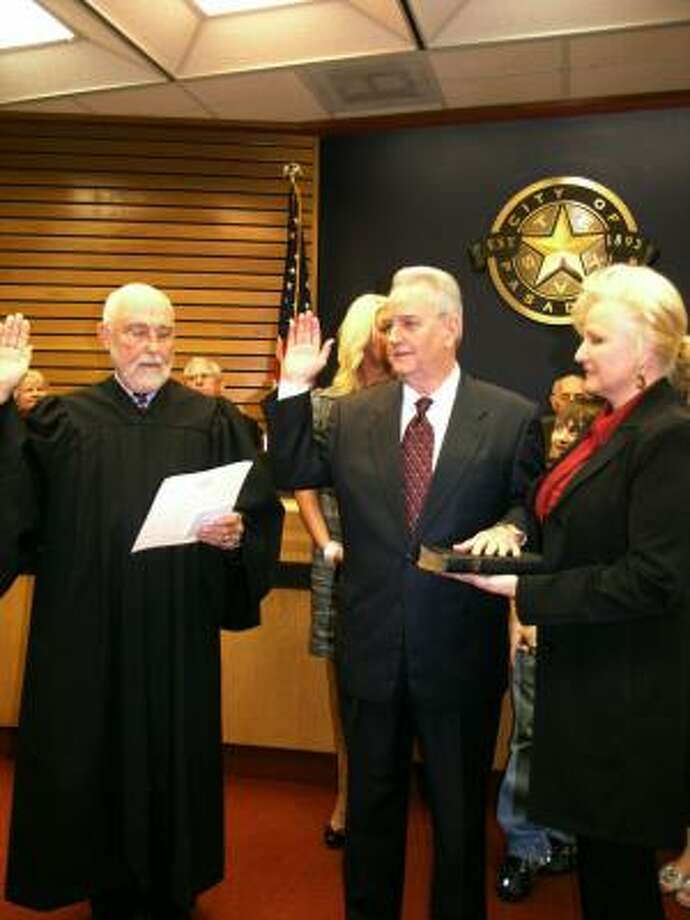 Pasadena municipal court Judge Lester Rorick, left, swears in Johnny Isbell as mayor of Pasadena, as his wife Jeannie Isbell, looks on. Photo:  Fannie Williams, For The Chronicle