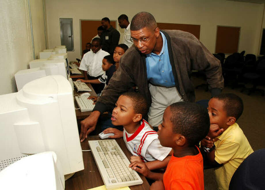 Walter August, pastor of The Church at Bethel's Family, helps Kameroe Senegal, left, 7; Xaviae Blake, 7; and Noah Shelby, 6, in the computer room at Bethel's Place, 12525 Fondren. Photo: George Wong, For The Chronicle