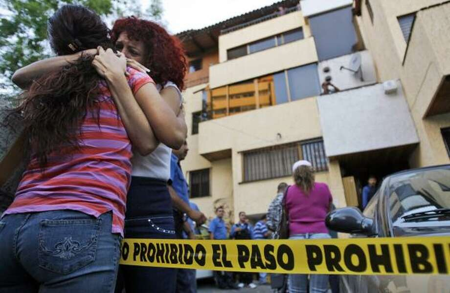 """A crowd gathers outside the law offices in Guadalajara where seven people were shot to death Thursday. Lawyers at the firm had unsuccessfully defended the son of Joaquin """"El Chapo"""" Guzman, head of the Sinaloa cartel. Photo: GUILLERMO ARIAS, ASSOCIATED PRESS"""