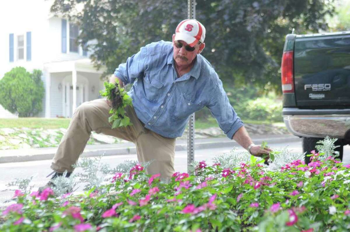Tom Mackey, of the Greenwich Parks Department, weeds a garden in the extreme heat on Sound Beach Avenue and Forest Avenue in Old Greenwich on Thursday, July 21, 2011.