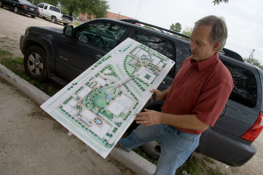 Alan Atkinson of AVA discusses an artist's rendering of the layout for Americas Plaza, currently under development in the East End. Photo: R. Clayton McKee, For The Chronicle