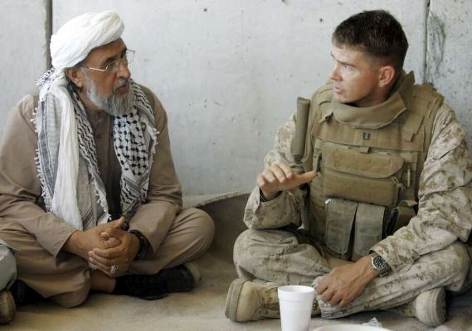 U.S. Marine Capt. Mike Hoffman, wearing issued body armor, talks with an Afghan village elder last year. The Marine Corps has ordered major changes to the armor amid troop complaints it's too heavy and restrictive. The vest currently used is the Marine Corps' third since 2001. Photo: RIC FRANCIS, ASSOCIATED PRESS